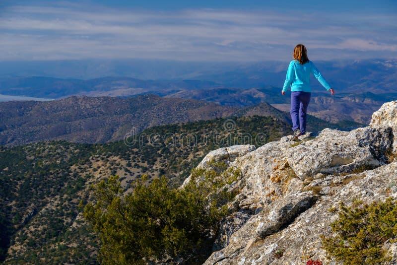 Αθλητική νέα γυναίκα που περπατά στη δύσκολη κορυφή του βουνού στοκ φωτογραφία με δικαίωμα ελεύθερης χρήσης