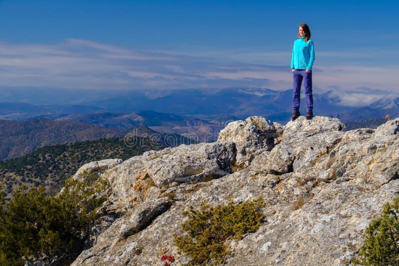 Αθλητική νέα γυναίκα που στέκεται στη δύσκολη κορυφή του βουνού α στοκ φωτογραφία