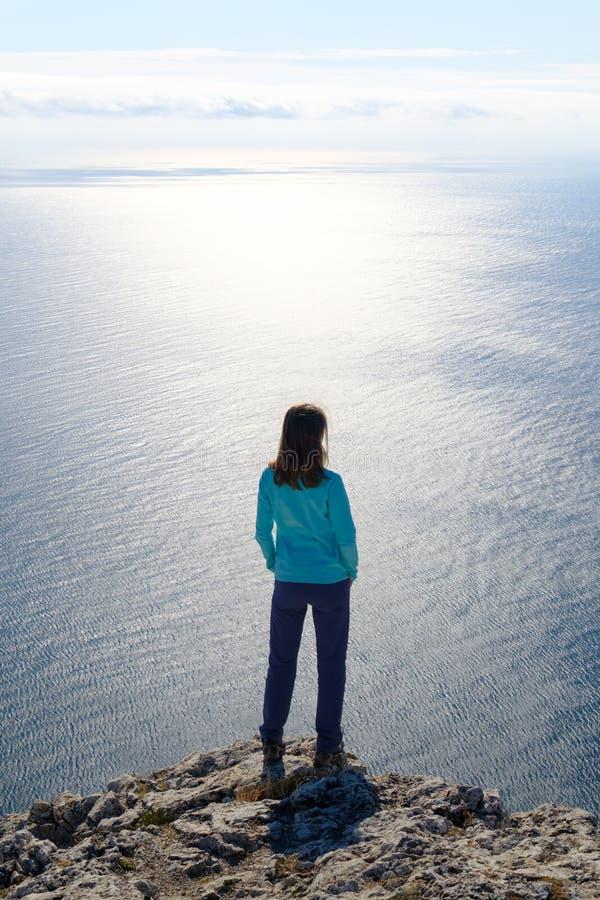 Αθλητική νέα γυναίκα που στέκεται στη δύσκολη κορυφή του βουνού ενάντια στο μπλε του ουρανού και της θάλασσας στοκ φωτογραφία