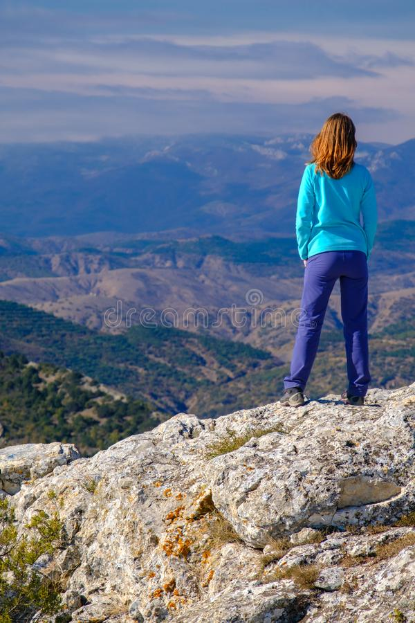 Αθλητική νέα γυναίκα που στέκεται στη δύσκολη κορυφή του βουνού στοκ εικόνες
