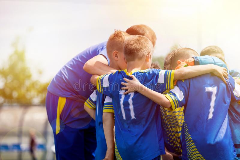 Αθλητική ομάδα παιδιών που διοργανώνει pep τη συζήτηση με το λεωφορείο Ομάδα ποδοσφαίρου παιδιών που παρακινείται από τον εκπαιδε στοκ φωτογραφίες με δικαίωμα ελεύθερης χρήσης