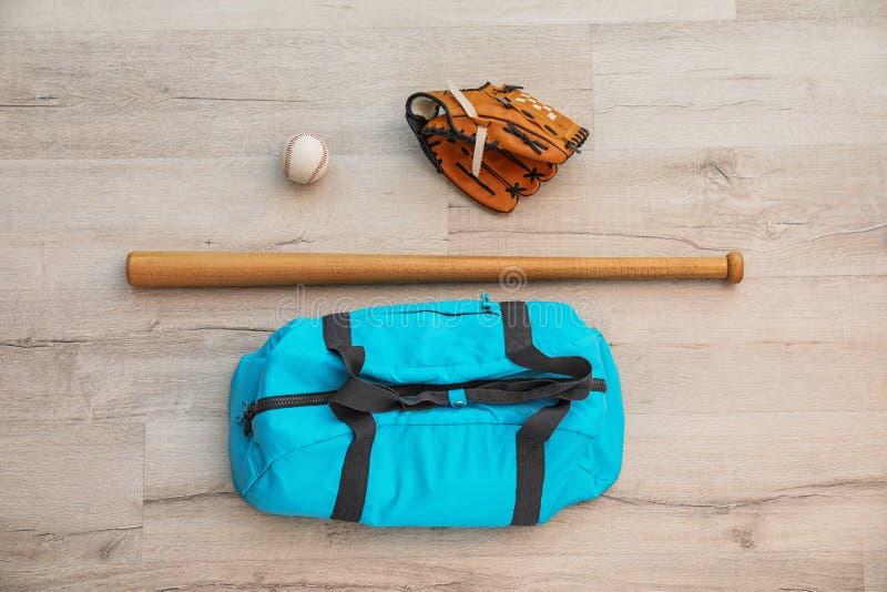 Αθλητική τσάντα, σφαίρα μπέιζ-μπώλ και ρόπαλο στο ξύλινο πάτωμα στοκ φωτογραφίες
