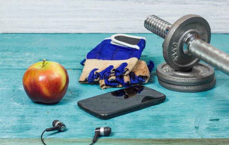 Αθλητικός εξοπλισμός Αλτήρες, ελεύθερα βάρη, αθλητικά γάντια, τηλέφωνο με τα ακουστικά στοκ εικόνες με δικαίωμα ελεύθερης χρήσης