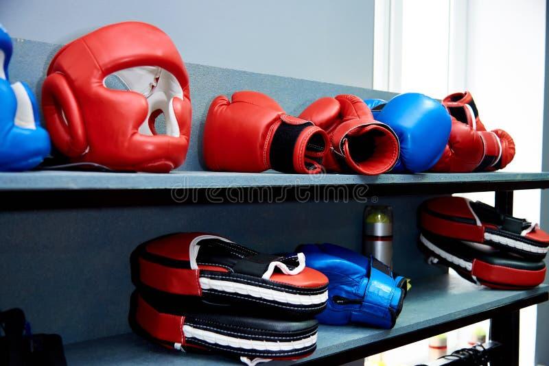 Αθλητικός εξοπλισμός για το σώμν με σώμα αγώνα Ένα προστατευτικό κράνος, γάντια και εγκιβωτίζοντας πόδια βρίσκονται σε ένα ράφι στοκ εικόνα