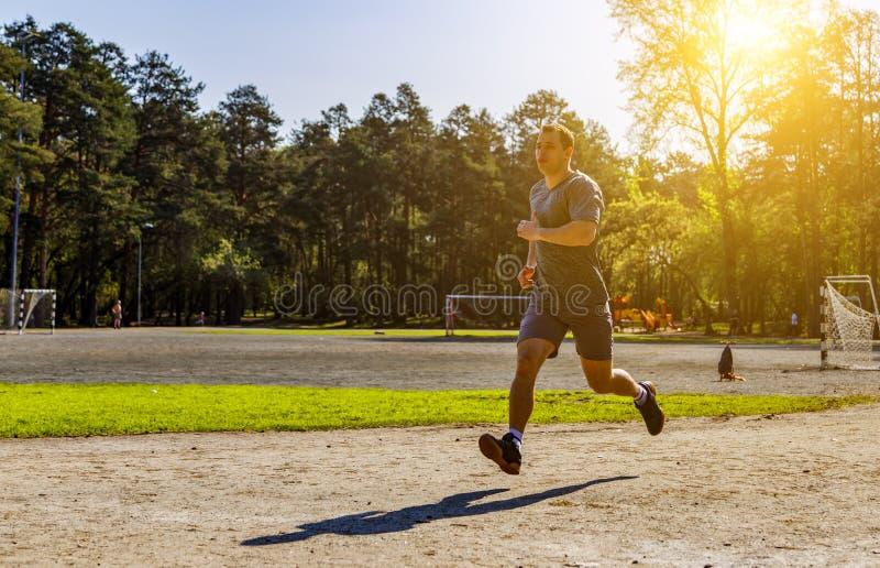 Αθλητικός καυκάσιος αθλητικός τύπος που τρέχει γρήγορα κάτω από τα sunrays στοκ φωτογραφίες με δικαίωμα ελεύθερης χρήσης