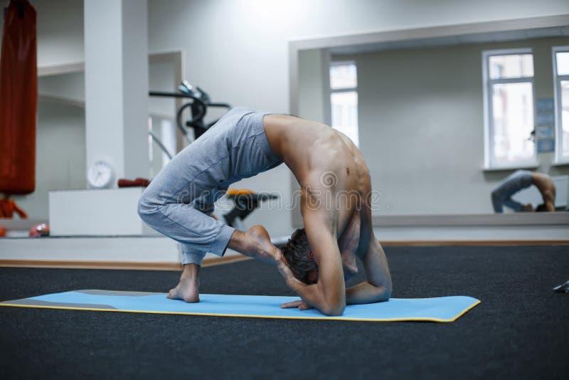 Αθλητικός μυϊκός νεαρός άνδρας που επιλύει, γιόγκα, pilates, ικανότητα στοκ φωτογραφίες με δικαίωμα ελεύθερης χρήσης
