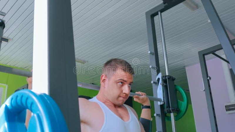Αθλητικός νεαρός άνδρας που κάνει τις ασκήσεις με το barbell στη γυμναστική, λέσχη ικανότητας στοκ εικόνες με δικαίωμα ελεύθερης χρήσης
