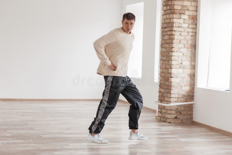 Αθλητικός νεαρός άνδρας που χορεύει στο άσπρο δωμάτιο, σύγχρονος χορός στοκ εικόνες με δικαίωμα ελεύθερης χρήσης