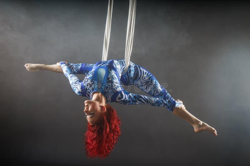Αθλητικός προκλητικός εναέριος καλλιτέχνης τσίρκων με redhead στο μπλε κοστούμι που χορεύει στον αέρα με την ισορροπία στοκ φωτογραφίες με δικαίωμα ελεύθερης χρήσης