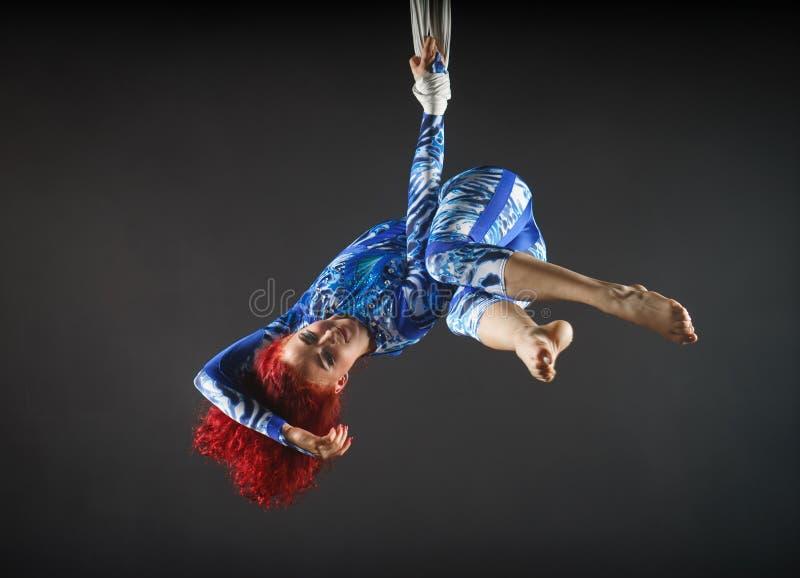 Αθλητικός προκλητικός εναέριος καλλιτέχνης τσίρκων με redhead στο μπλε κοστούμι που χορεύει στον αέρα με την ισορροπία στοκ φωτογραφίες