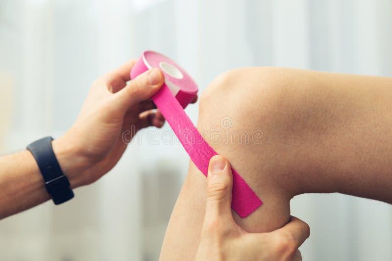Αθλητικός τραυματισμός - θεράπων που τοποθετεί την ταινία kinesio στο γόνατο στοκ εικόνες με δικαίωμα ελεύθερης χρήσης