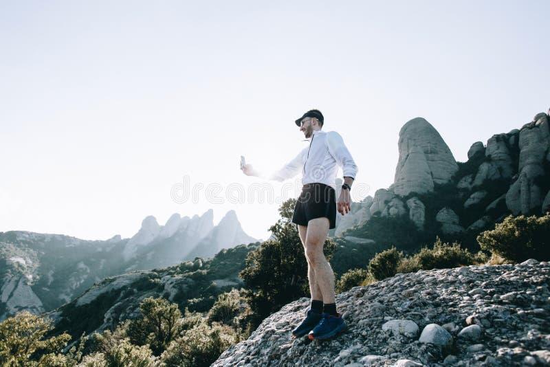 Αθλητικός τύπος ή αθλητής με το smartphone στο βουνό στοκ φωτογραφίες