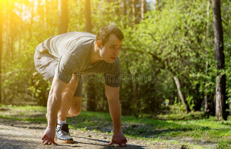Αθλητικός τύπος που στέκεται στη θέση έτοιμη να αρχίσει τη φυλή και κοιτάζοντας μπροστά στοκ εικόνα