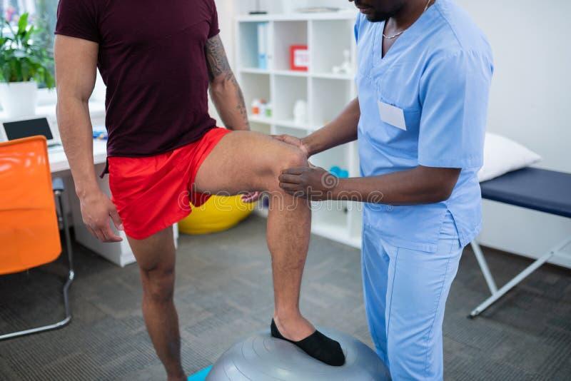 Αθλητικός τύπος στα κόκκινα σορτς που βάζει το πόδι στη σφαίρα έλατου που στέκεται κοντά στο θεράποντα στοκ φωτογραφία με δικαίωμα ελεύθερης χρήσης