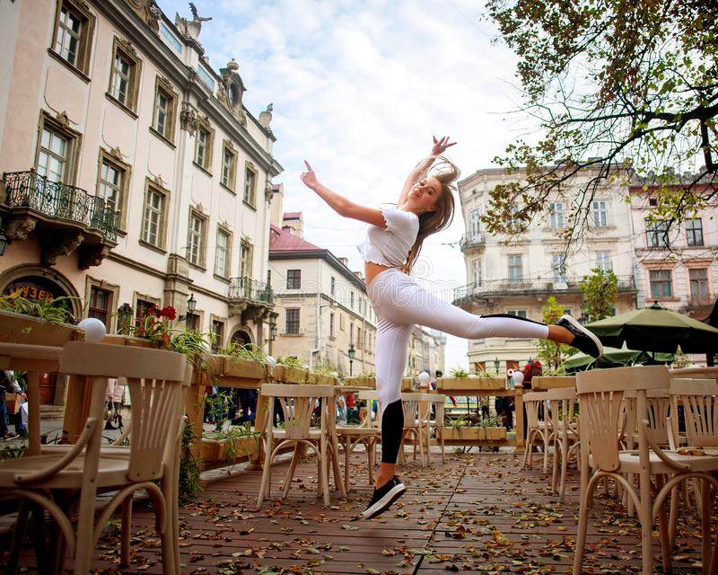 Αθλητικός gymnast κοριτσιών που πηδά στην οδό της παλαιάς πόλης το καλοκαίρι στοκ φωτογραφία