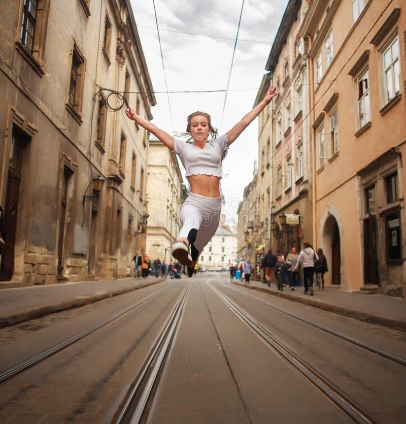 Αθλητικός gymnast κοριτσιών που πηδά στην οδό της παλαιάς πόλης το καλοκαίρι στοκ φωτογραφία με δικαίωμα ελεύθερης χρήσης