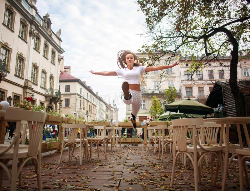 Αθλητικός gymnast κοριτσιών που πηδά στην οδό της παλαιάς πόλης το καλοκαίρι στοκ εικόνες