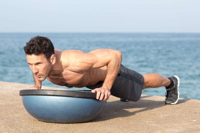 Αθλητικό άτομο που κάνει το ώθηση-UPS στην πλατφόρμα ισορροπίας στοκ εικόνες