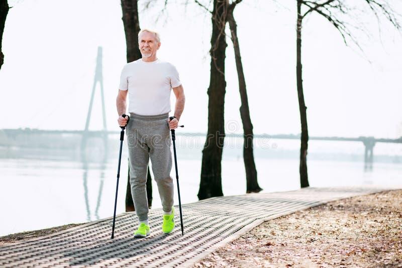 Αθλητικό ανώτερο άτομο που δοκιμάζει το αθλητικό περπάτημα στοκ εικόνες με δικαίωμα ελεύθερης χρήσης