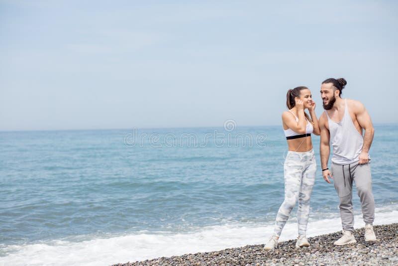 Αθλητικό ζεύγος που θερμαίνει, πόδια τεντώματος μαζί σε μια παραλία στοκ εικόνες