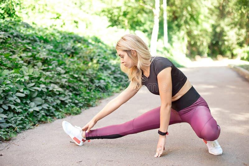 Αθλητικό κορίτσι ικανότητας sportswear μόδας που κάνει την άσκηση ικανότητας γιόγκας στην οδό, υπαίθριος αθλητισμός, αστικό ύφος στοκ φωτογραφία
