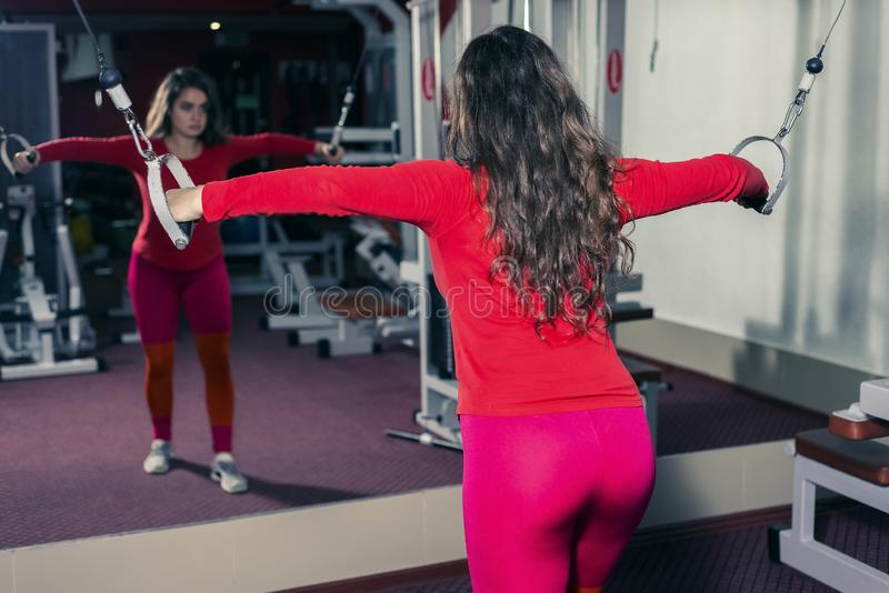 Αθλητικό κορίτσι που συμμετέχεται στη γυμναστική στον προσομοιωτή αθλητικά ικανότητα και η γυναίκα εξετάζει του καθρέφτη στοκ φωτογραφία με δικαίωμα ελεύθερης χρήσης
