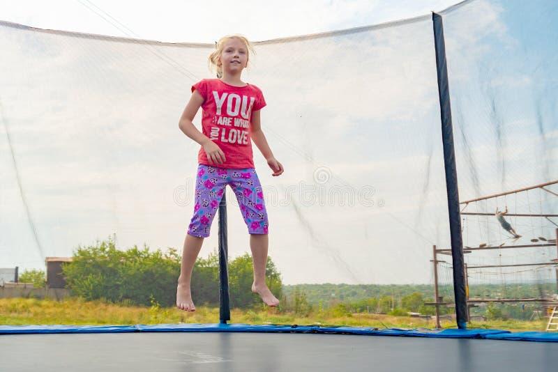 Αθλητικό κορίτσι σε μια κόκκινη μπλούζα που πηδά σε ένα τραμπολίνο στοκ φωτογραφία με δικαίωμα ελεύθερης χρήσης