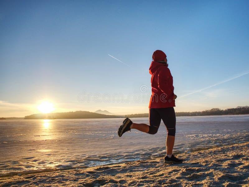 Αθλητικό κορίτσι στα χειμερινά ενδύματα που τρέχουν μακριά στον ορίζοντα της παγωμένης θάλασσας στοκ εικόνα με δικαίωμα ελεύθερης χρήσης