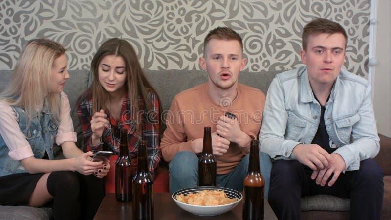Αθλητικό παιχνίδι προσοχής αγοριών στη TV στο σπίτι, που πίνει το οινόπνευμα, ενώ κορίτσια που κάνουν σερφ Διαδίκτυο στο smartpho στοκ φωτογραφία με δικαίωμα ελεύθερης χρήσης