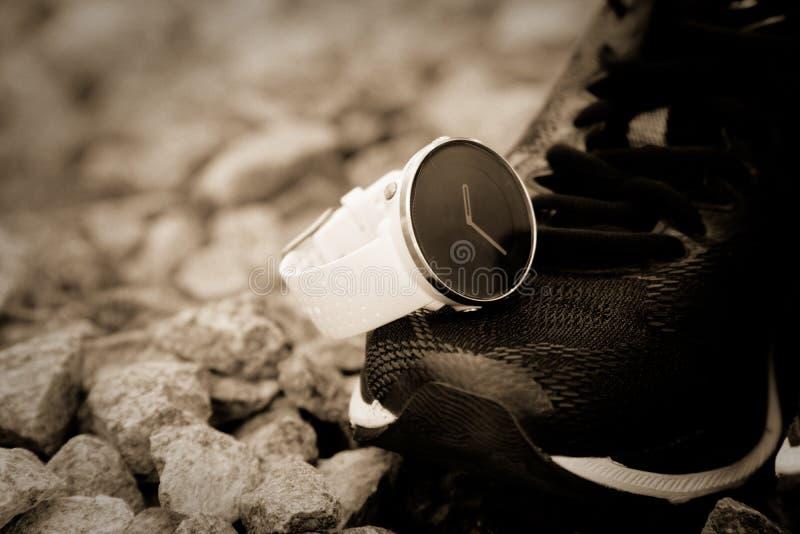 Αθλητικό ρολόι για το crossfit και triathlon στα τρέχοντας παπούτσια Έξυπνο ρολόι για την καταδίωξη της καθημερινής κατάρτισης δρ στοκ εικόνες