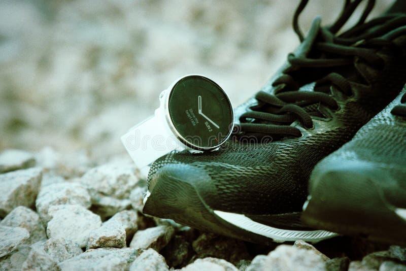 Αθλητικό ρολόι για το crossfit και triathlon στα τρέχοντας παπούτσια Έξυπνο ρολόι για την καταδίωξη της καθημερινής κατάρτισης δρ στοκ φωτογραφία με δικαίωμα ελεύθερης χρήσης
