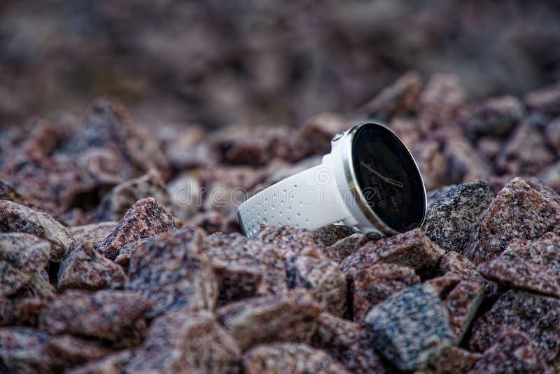 Αθλητικό ρολόι για το triathlon στο αμμοχάλικο γρανίτη Έξυπνο ρολόι για την καταδίωξη της καθημερινής κατάρτισης δραστηριότητας κ στοκ φωτογραφία με δικαίωμα ελεύθερης χρήσης