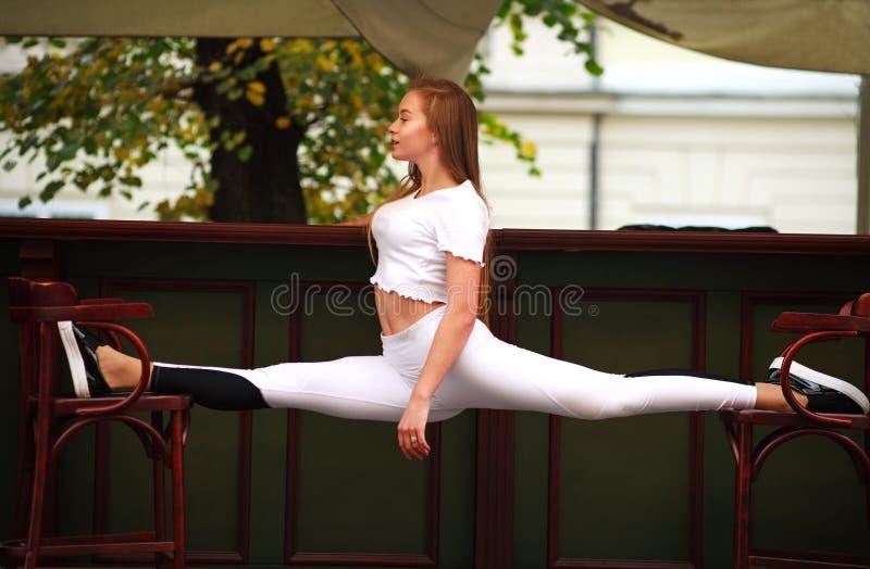 Αθλητικό gymnast κορίτσι που κάνει τις τεντώνοντας διασπάσεις άσκησης ικανότητας στοκ εικόνες