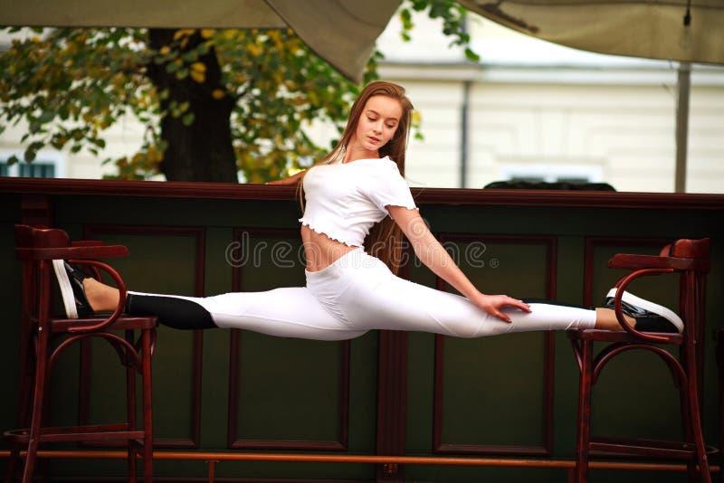 Αθλητικό gymnast κορίτσι που κάνει τις τεντώνοντας διασπάσεις άσκησης ικανότητας στοκ εικόνα