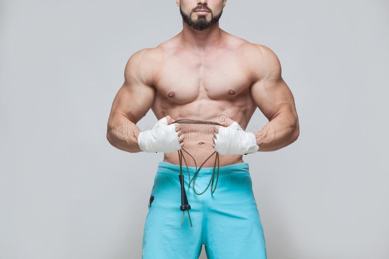 Αθλητισμός, δραστηριότητα Μυϊκός μαχητής kickbox με το πηδώντας σχοινί Μυϊκό γκρίζο υπόβαθρο ατόμων στοκ εικόνα