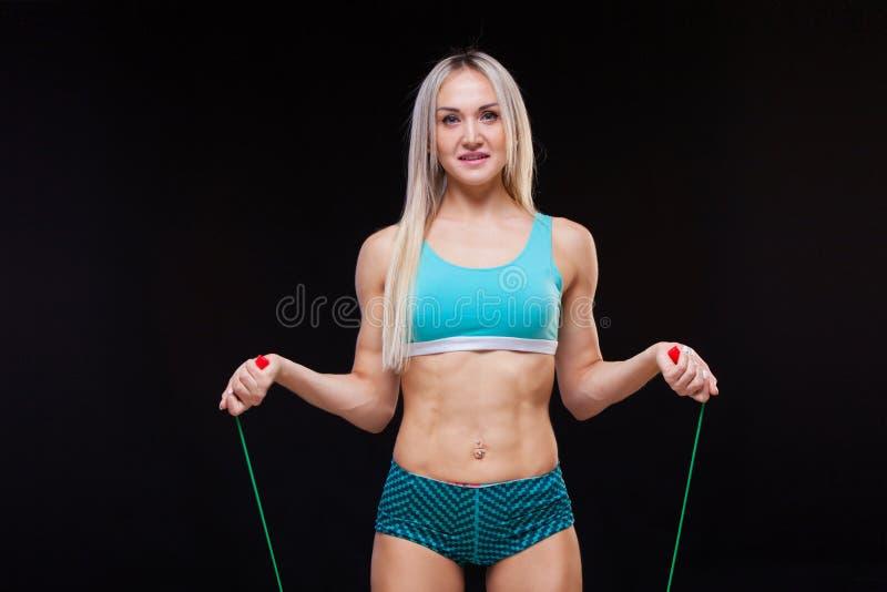 Αθλητισμός, δραστηριότητα Χαριτωμένη γυναίκα με το πηδώντας σχοινί Μυϊκό μαύρο υπόβαθρο γυναικών στοκ εικόνες