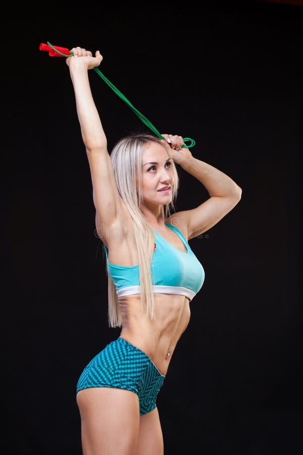 Αθλητισμός, δραστηριότητα Χαριτωμένη γυναίκα με το πηδώντας σχοινί Μυϊκό μαύρο υπόβαθρο γυναικών στοκ φωτογραφία με δικαίωμα ελεύθερης χρήσης