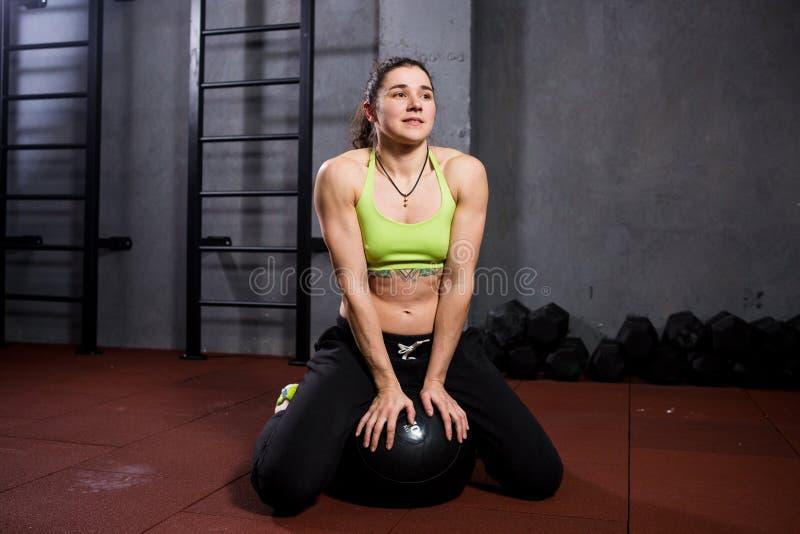 Αθλητισμός και υγεία θέματος Ισχυρή μυϊκή καυκάσια γυναίκα στη συνεδρίαση γυμναστικής μαύρο σε έναν βαρύ που γεμίζεται fitball πα στοκ φωτογραφίες με δικαίωμα ελεύθερης χρήσης