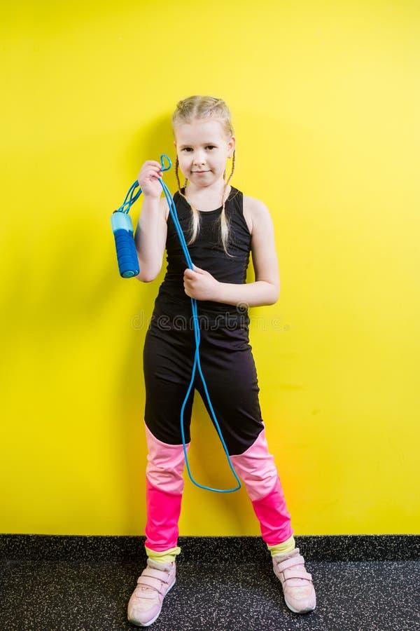 Αθλητισμός και υγεία θέματος Όμορφο καυκάσιο κορίτσι παιδιών με τις πλεξίδες που θέτουν το κίτρινο υπόβαθρο με το χαμόγελο λίγος  στοκ φωτογραφίες με δικαίωμα ελεύθερης χρήσης