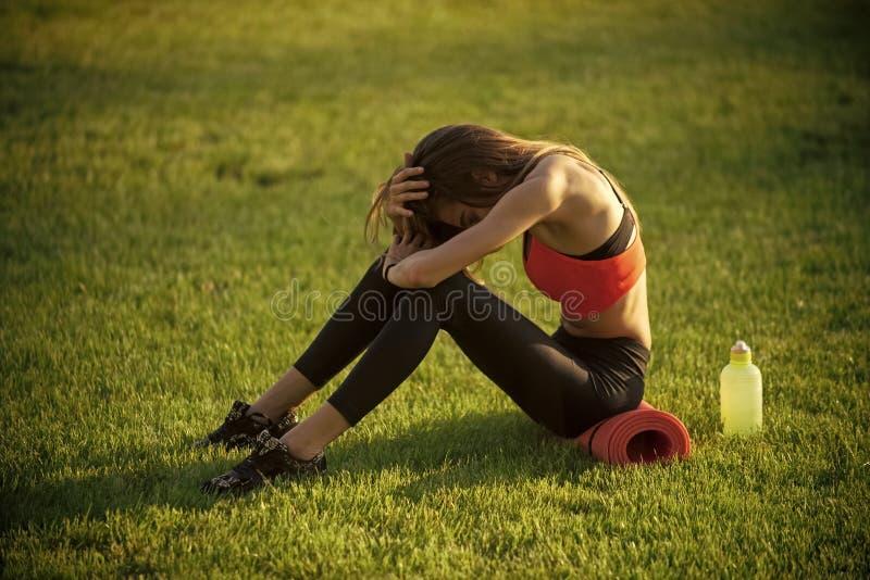 Αθλητισμός, που εκπαιδεύει, workout Υγεία, bodycare, wellness Η φίλαθλος κάθεται στην πράσινη χλόη με τον εξοπλισμό γυμναστικής σ στοκ εικόνα