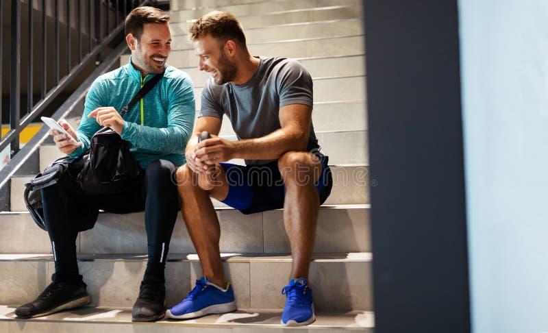 Αθλητισμός, φυσική κατάσταση, υγιεινός τρόπος ζωής και έννοια των ανθρώπων Χαρούμενοι φίλοι άνδρες που μιλάνε μετά την προπόνηση στοκ εικόνες