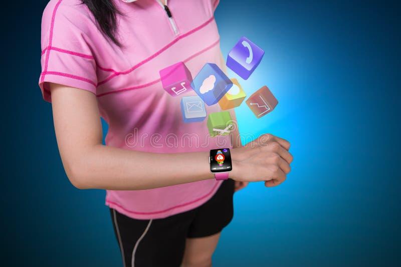Αθλήτρια που φορά την οθόνη επαφής smartwatch με το ζωηρόχρωμο app ico στοκ εικόνα