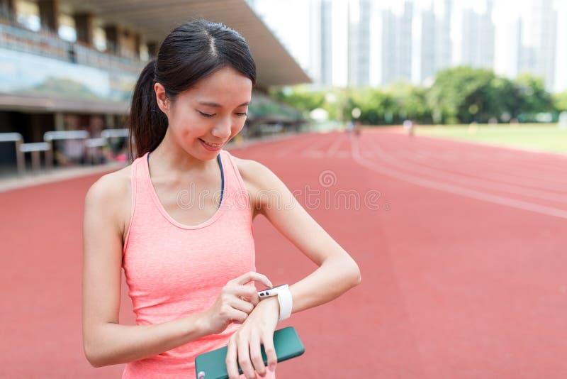 Αθλήτρια που χρησιμοποιεί το φορετό έξυπνο ρολόι στο αθλητικό στάδιο στοκ φωτογραφία με δικαίωμα ελεύθερης χρήσης