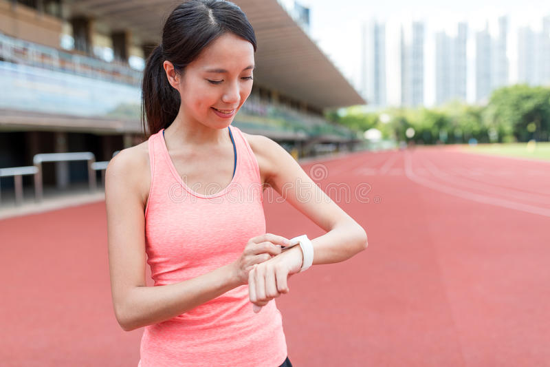 Αθλήτρια που χρησιμοποιεί το φορετό έξυπνο ρολόι στοκ φωτογραφίες