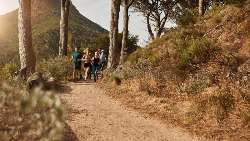 Αθλητές που τρέχουν μαζί μέσω των ιχνών στη βουνοπλαγιά στοκ εικόνα με δικαίωμα ελεύθερης χρήσης