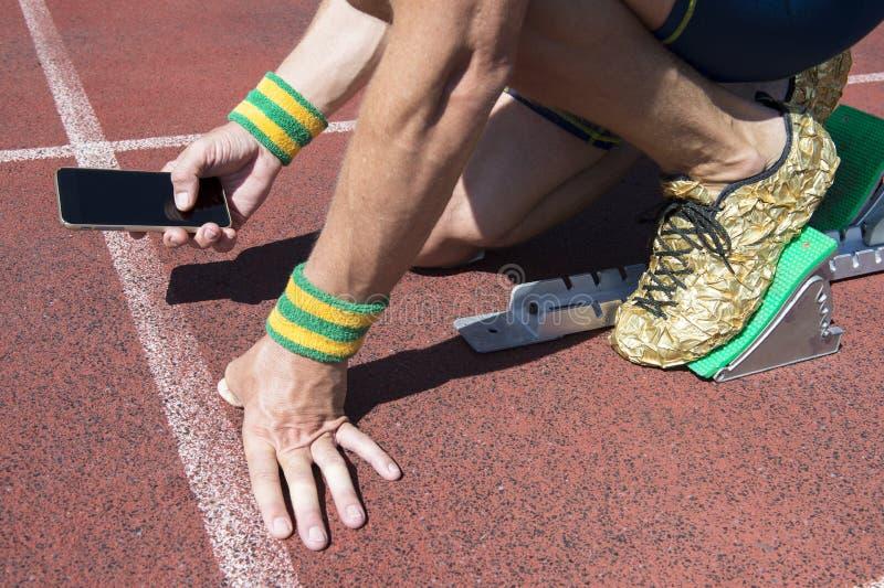 Αθλητής που χρησιμοποιεί το κινητό τηλέφωνο στη διαδρομή στοκ φωτογραφία