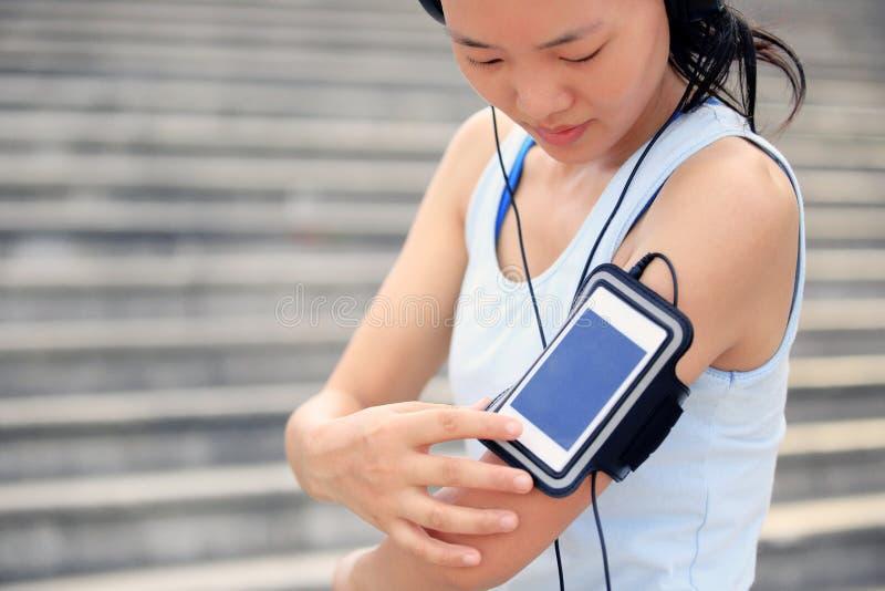 Αθλητής δρομέων που ακούει τη μουσική στα ακουστικά από τον έξυπνο τηλεφωνικό mp3 φορέα στοκ φωτογραφίες με δικαίωμα ελεύθερης χρήσης