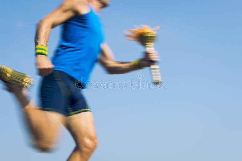 Αθλητής Torchbearer που τρέχει με το μπλε ουρανό αθλητικών φανών στοκ εικόνες