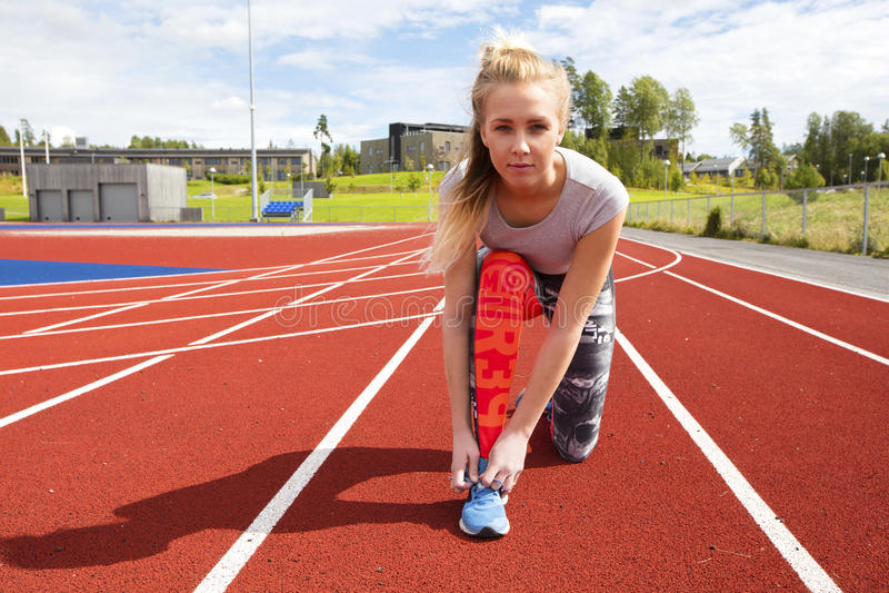 Αθλητικά θηλυκά δένοντας κορδόνια δρομέων στο τρέξιμο της διαδρομής στοκ εικόνα με δικαίωμα ελεύθερης χρήσης