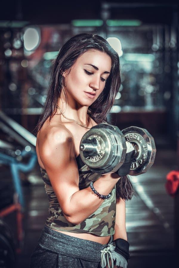 Αθλητική γυναίκα που αντλεί επάνω muscules με τους αλτήρες στοκ εικόνα με δικαίωμα ελεύθερης χρήσης